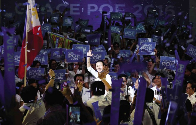 Sen. Grace Poe waves to her supporters while blue and wife confetti. Photo from Marianne Bermudez of the Philippine Star.