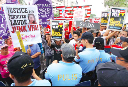 Militant protesters stage a rally in front of the US Embassy against US military presence in the Philippines following the slay of transgender Jennifer Laude. Photo from Manila Bulletin (mb.com.ph)